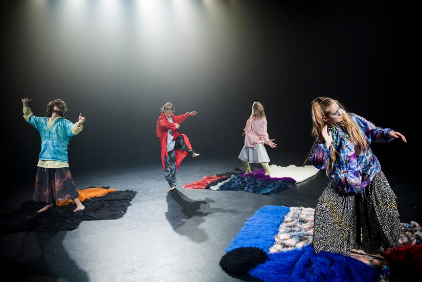 Four dancers wearing colourful clothes.