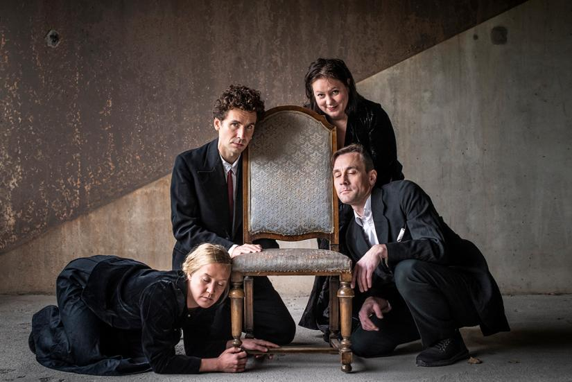 Four people leaning on an old fashioned chair