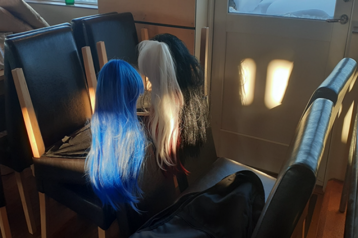 three wigs on a chair