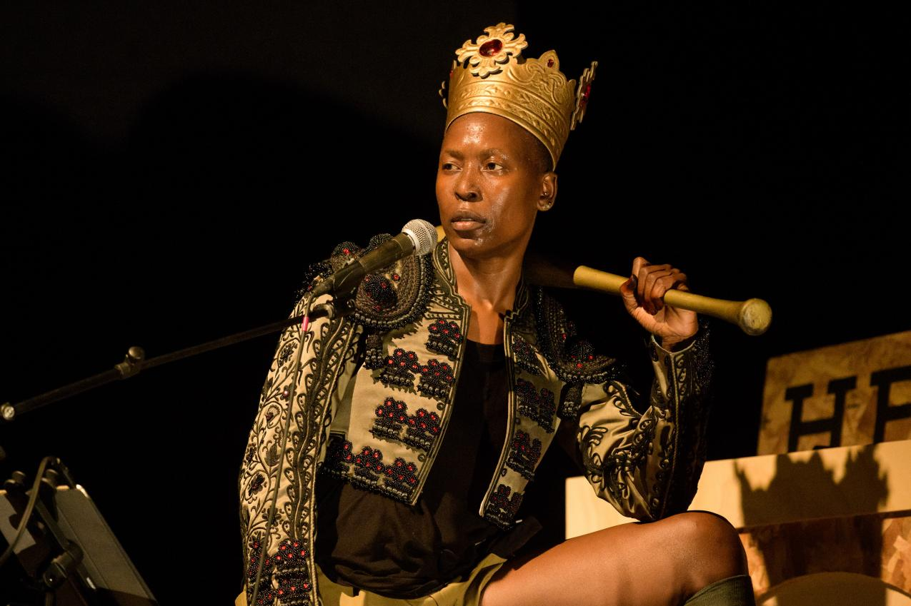 A black person wearing a crown, holding a golden baseball bat on their sholder.