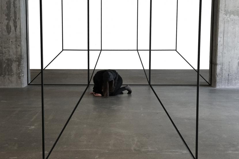 A figure crouch on the floor in a gallery like space, which also has metallic frames in it.