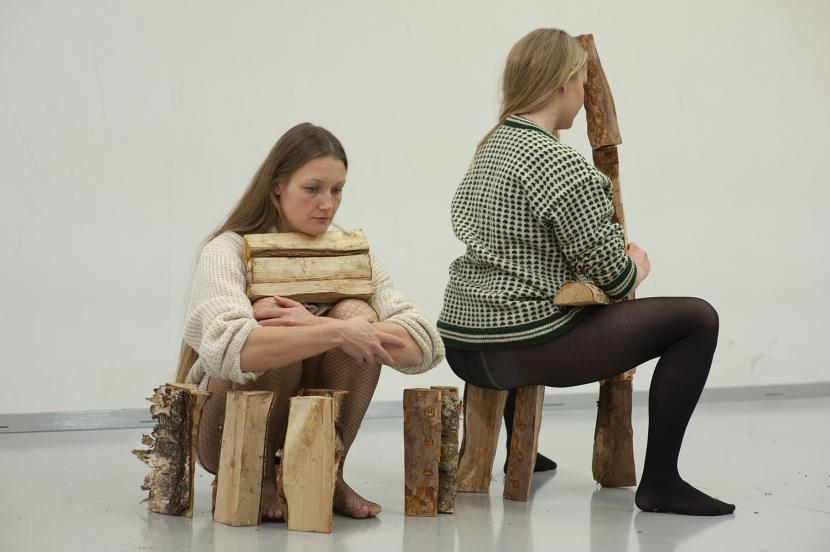 Two assumed women, sitting with blocks of wood in their lap and around them.